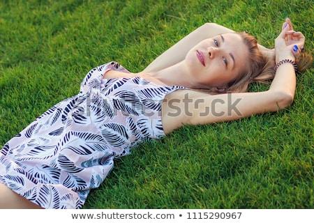 Blond Woman Wearing Sun Dress Lying in Grass Stock photo © dash