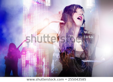 Beautiful woman listening to music with headphones and singing. Concept  of live music and party Stock photo © Ainat