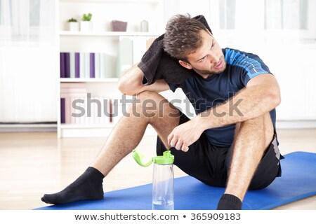 Tired man wiping sweat after workout Stock photo © d13