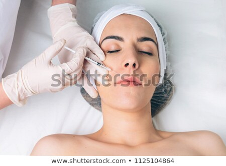 Young pretty woman getting cosmetic injection in the face like a Stock photo © dashapetrenko