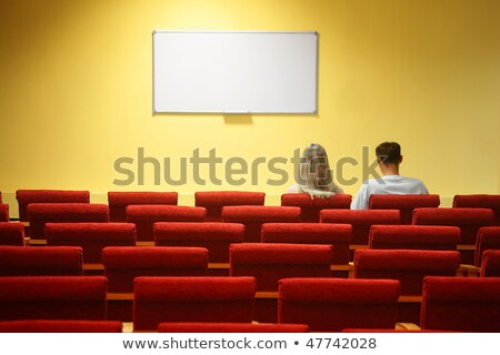 Empty conference hall. rows of a chairs. focus on a third row. man and woman sitting in chairs Stock photo © Paha_L