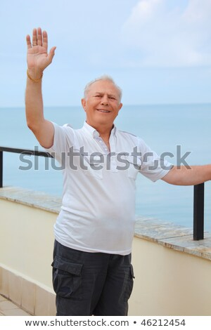 smiling senior on veranda near seacoast, lifted hand upwards Stock photo © Paha_L