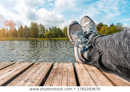 man with crossed legs relaxing on riverbank pier stock photo © stevanovicigor