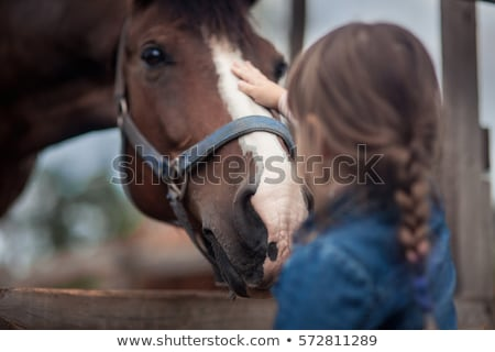 smiling pretty young woman cowgirl in hat with her horse stock photo © deandrobot