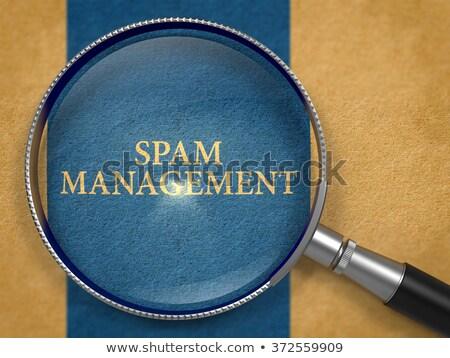 Spam Management through Loupe on Old Paper. Stock photo © tashatuvango
