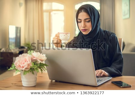 A Middle Eastern businessman talking to a woman using a laptop Stock photo © monkey_business