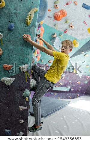 Foto stock: Boy In Sportswear Looking At You While Holding By Small Rocks And Climbing