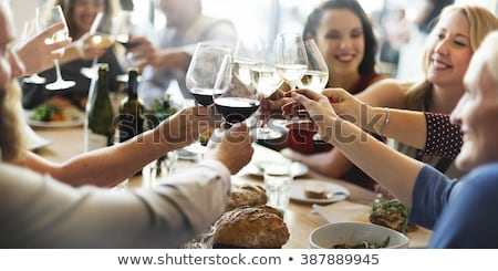 People in an Italian restaurant drinking wine and eating pasta Stock photo © Kzenon