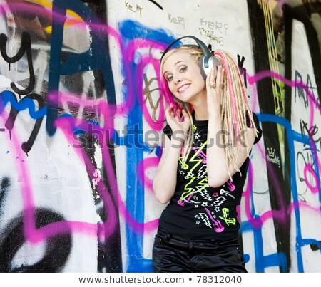 young woman with headphones standing at graffitti wall stock photo © phbcz