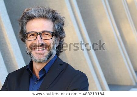 maduro · sorridente · homem · de · negócios · em · pé · luz - foto stock © HASLOO