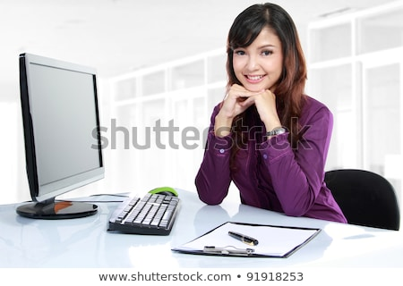 portrait of a pretty businesswoman sitting at her desk stock photo © hasloo