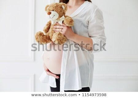 Stock photo: Pregnant woman holding a big teddy bear