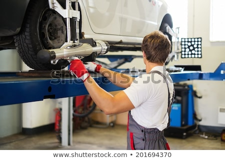 Stock photo: Young serviceman checking wheel alignment  in a car workshop
