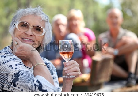 Senior woman enjoying a glass of rose wine with friends on a picnic Stock photo © photography33