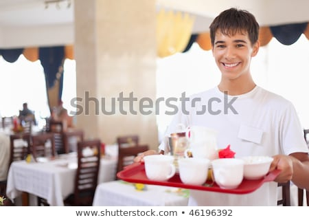 young smiling affable waiter keeps tray with dishes at restauran Stock photo © Paha_L