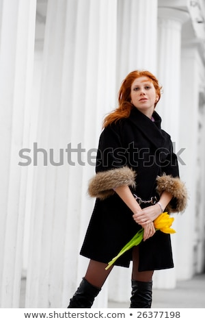 Outdoor portrait of beautiful redhead young woman near column. Bouquet of red flowers. stock photo © traza