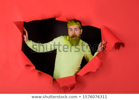 Young, smart guy looking through the hole Stock photo © konradbak