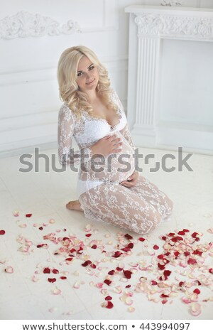 beautiful smiling pregnant woman sitting on floor with red rose stock photo © victoria_andreas