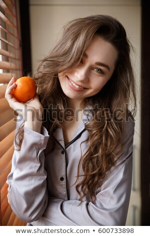 Vertical image of happy woman holding tangerine Stock photo © deandrobot
