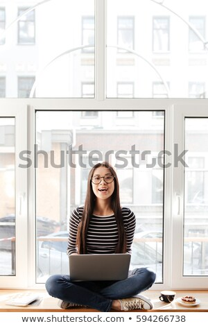 Happy Asian woman on windowsill with laptop stock photo © deandrobot