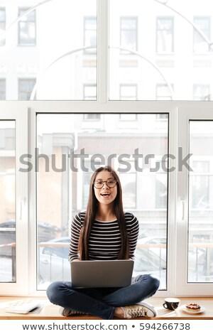 счастливым · азиатских · женщину · подоконник · ноутбука · очки - Сток-фото © deandrobot