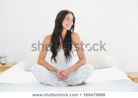 Woman sitting on bed smiling stock photo © monkey_business