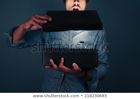 man opening a box with something exciting inside it Stock photo © ichiosea