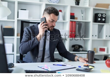 A man is sitting at the desk at the office, talking on the phone and holding a glass of coffee. Stock photo © Traimak
