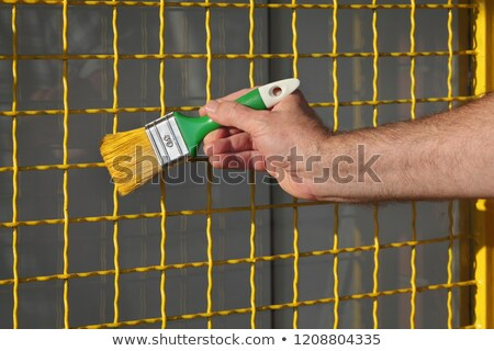 Worker painting metal protective net to yellow color Stock photo © simazoran