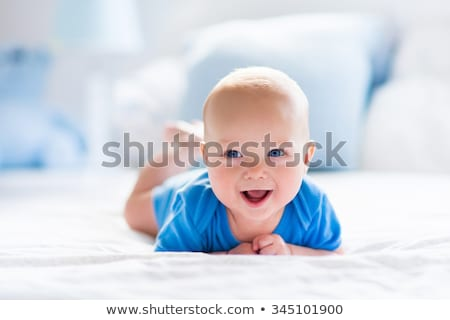 portrait of a baby boy on the bed in bedroom stock photo © lopolo