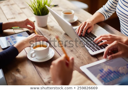 Group of people with devices in hands working on laptops, tablet Stock photo © ra2studio
