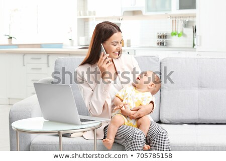 working mother with baby calling on smartphone stock photo © dolgachov