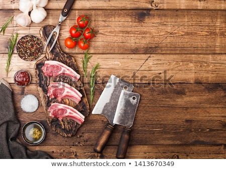 Fresh raw butchers lamb beef cutlets on chopping board with vintage meat hatchets on wooden backgrou Stock photo © DenisMArt