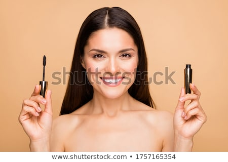 Stock photo: Cosmetics products. Close up of cheerful young woman with colorful makeup. Beauty portrait of female