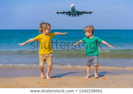 Two happy boys have fun on the beach watching the landing planes. Traveling on an airplane with kids Stock photo © galitskaya