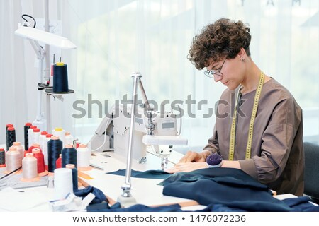 Pretty young seamstress sitting by sewing machine and processing blue textile Stock photo © pressmaster