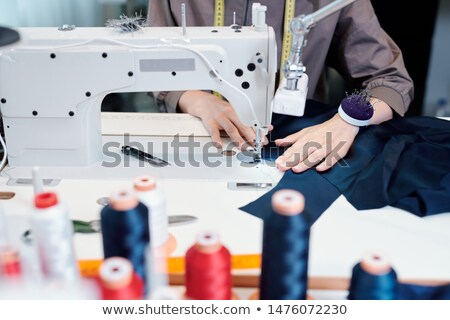female tailor hands moving piece of blue textile while sewing by machine stock photo © pressmaster
