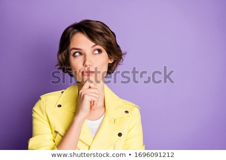 Young woman with questioning look isolated on yellow background. Stock photo © lichtmeister