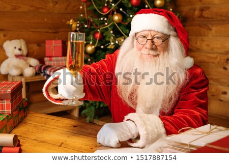 Santa Claus with flute of champagne toasting for Christmas by wooden table Stock photo © pressmaster