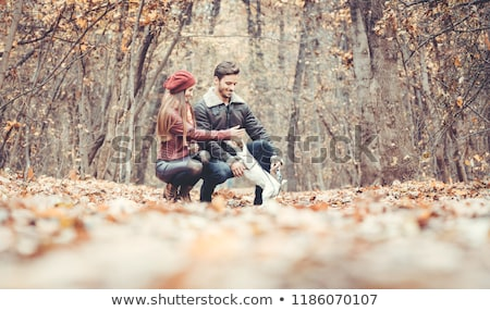 Сток-фото: Woman And Man Petting The Dog Walking Her In A Colorful Fall Setting
