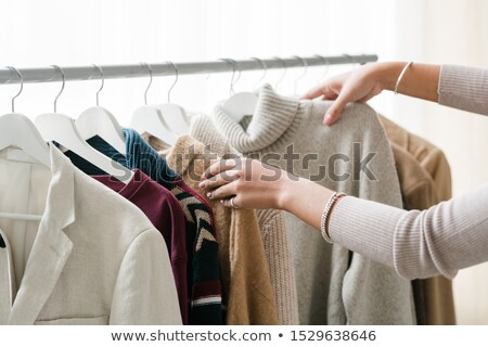 Hands of young female shopper choosing warm knitted and woolen clothes Stock photo © pressmaster