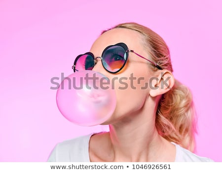 Stock photo: young woman or teenage girl blowing bubble gum