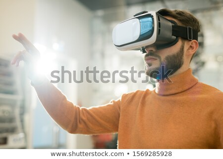 Serious man in vr goggle touching virtual display while making presentation Stock photo © pressmaster