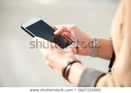 Hand of young mobile woman with smartphone scrolling through contacts Stock photo © pressmaster