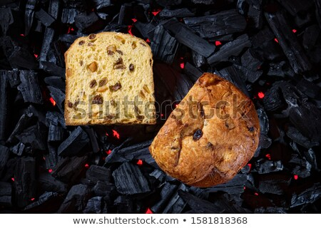 Panettone placed on black charcoal with red fire background Stock photo © georgemuresan