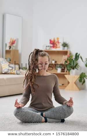 Pretty young active woman with dreadlocks sitting on the floor with crossed legs Stock photo © pressmaster