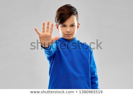 boy in blue hoodie making stopping gesture Stock photo © dolgachov