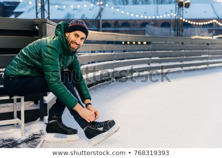 Cheerful man with appealing appearance laces up skates, sitts on Stock photo © vkstudio