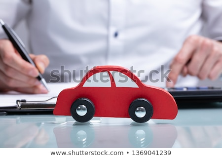 Toy Car In Front Of Businessman Calculating Loan Stock photo © AndreyPopov