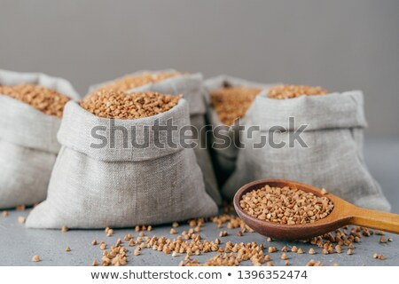 Dieting and nutrition concept. Brown buckwheat harvested in bags, isolated over grey background. Dry Stock photo © vkstudio